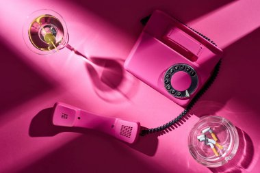 Top view of pink telephone, cocktail and astray with cigarette butts on pink surface