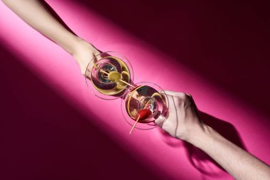 Cropped view of man and woman holding cocktails on pink background with shadow