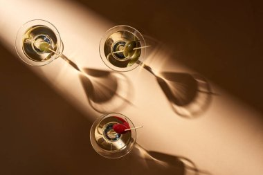 Top view of martini cocktails with olives on beige background