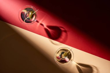 Top view of two cocktails on red and beige background