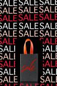Papiereinkaufstasche mit rotem Griff isoliert auf schwarz mit Verkaufsillustration