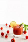 Bloody Mary koktejl ve skle zdobené vápnem a celerem izolované na bílém s rajčaty