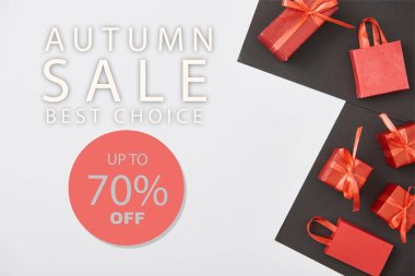 Top view of red gift boxes and shopping bags on white and black background with up to 70 percent off autumn sale illustration stock vector