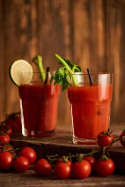 Selective focus of bloody mary cocktail in glasses with lime and celery on wooden background with tomatoes stock vector