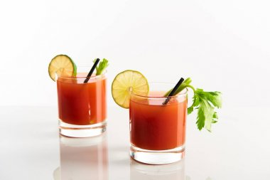 Bloody mary cocktail in glasses garnished with lime and celery isolated on white stock vector