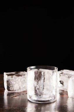 Glass near ice cubes isolated on black stock vector