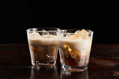 fresh white russian cocktail in glasses isolated on black
