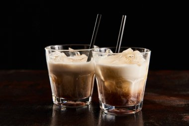 fresh white russian cocktail in glasses with straws isolated on black