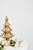 shiny Christmas tree and baubles on white surface isolated on grey