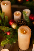 close up of burning candles with spruce branches and christmas balls on wooden table