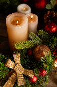 close up of burning candles with spruce branches, bow and christmas balls on wooden table