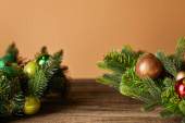 Fotografie decorative spruce branches with christmas balls on wooden table on beige