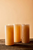 three festive burning candles on wooden table on beige