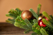 festive spruce branches with christmas balls on wooden table on beige