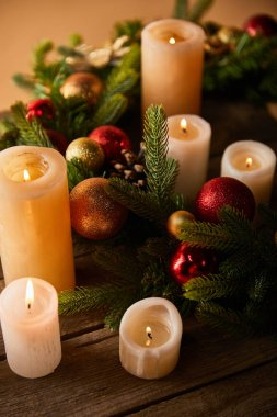burning candles with spruce wreath and christmas balls on wooden table