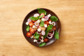 top view of fresh Italian vegetable salad panzanella served on plate on wooden table