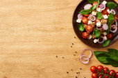 top view of delicious Italian vegetable salad panzanella served on plate on wooden table near fresh ingredients