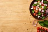 vrchní pohled na vynikající italský zeleninový salát panzanella podávané na talíři na dřevěném stole v blízkosti čerstvých ingrediencí