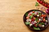 delicious Italian vegetable salad panzanella served on plate on wooden table near fresh ingredients