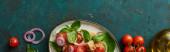 vrchní pohled na vynikající italský zeleninový salát panzanella podávané na talíři na texturovaném zeleném povrchu se ingrediencemi, panoramatický výstřel