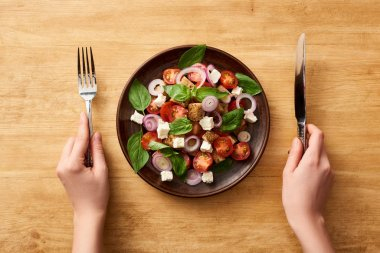 cropped view of woman eating panzanella salad with knife and fork at wooden table
