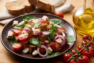 Selective focus of delicious Italian vegetable salad panzanella served on plate on wooden table near fresh tomatoes, olive oil and bread stock vector