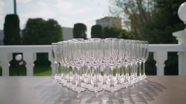 Sektgläser. Catering auf der Straße. Schöne Urlaubstisch Gläser Wein glassesttwo Reihen Gläser auf einem Tisch mit einer weißen Tischdecke Gläser auf hohen Beinen platziert ein Glas Wein auf festlichen Tisch. Nahaufnahme. Außengastronomie.
