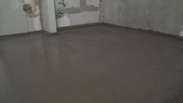 Stavitel v bytě pokládá betonovou podlahu. Vyrovnávám podlahu s dlouhou špachtlí. Stavitel srovná laťku. Podlaha ležící doma.