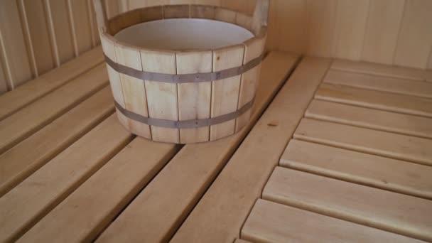 Dampfbad in einem finnischen Bad mit einem Holzbecken mit Wasser zum Einweichen. Sauna mit Holzbecken.
