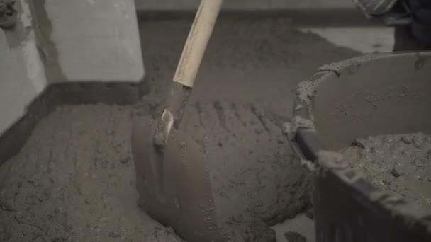 Naplnit podlahu betonovou maltou. Dělník se vyrovná s obracečem. Pracovník aplikuje řešení lopatou na vyrovnání betonové podlahy.