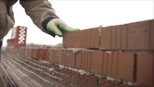 Zedník pracující na staveništi cihlové zdi. Zedník pokládal na staveniště další řadu cihel. Dělník postaví cihlovou zeď