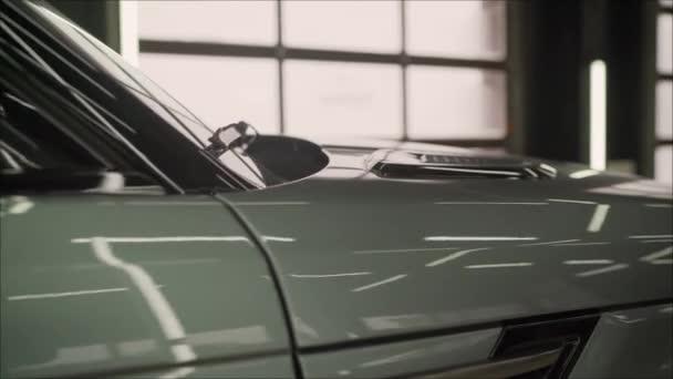 auto na servisní garáži s mechanickým nářadím pro opravované auto, automechanik pracující v servisním středisku. Drahé bílé SUV na čerpací stanici