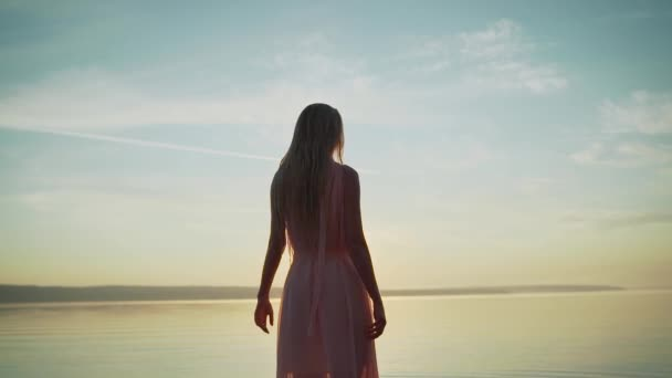 Girl in a light dress on the beach at sunrise. beautiful women in a light pink dress walking along the beach at dawn. Good morning and relaxation. Young beautiful girl stands in the water in a light