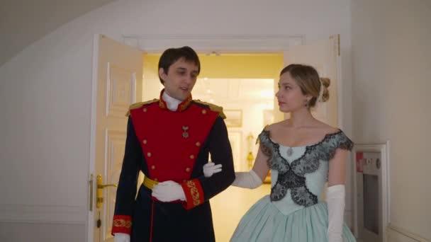 Der Typ in Uniform lädt das Mädchen zum Tanzen ein. Liebesgeschichte Typ lädt ein Mädchen in einem alten, schönen Kleid zum Tanzen ein. Ein Mann und ein Mädchen in Kleidern aus dem 19. Jahrhundert.