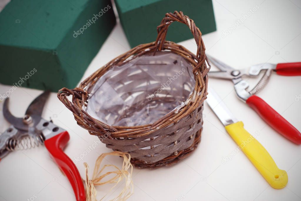 Composition of florist equipment tools with florist foam and basket on white background