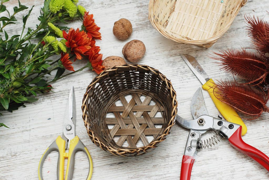 Decorative bascket and tools for creating the bouquet and greeting card on the desktop. Florist work space or table.