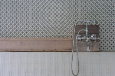 Vintage style shower head set on wooden shelf above over bathtub in outdoor bathroom. (Selective focus)