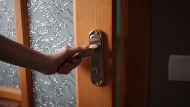 Frau Hand öffnet Holztür. in der Hand einen goldenen Türgriff