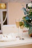 zwei Gläser Champagner und Kissen mit Ringen auf dem Tisch für die Trauung