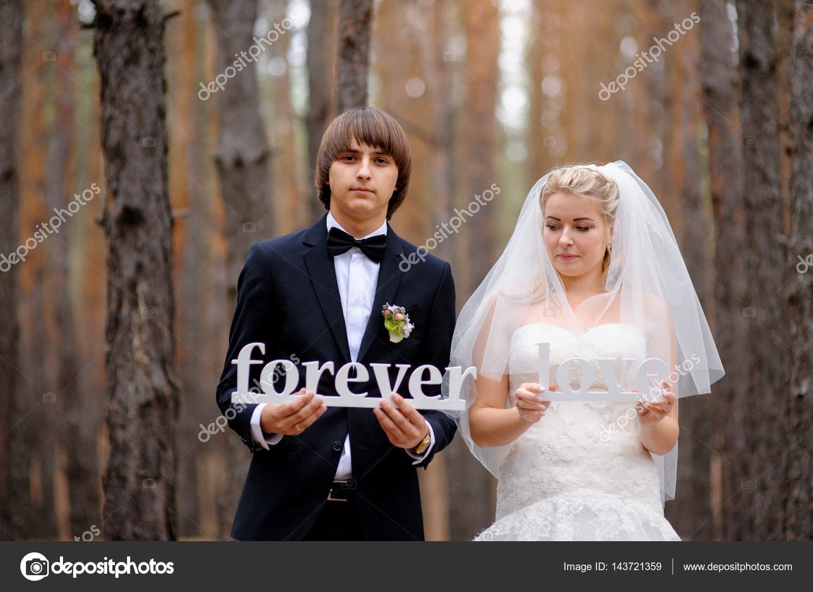 bride and groom holding wooden letters love forever stock photo