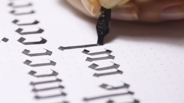Woman writes pen with calligraphic letters