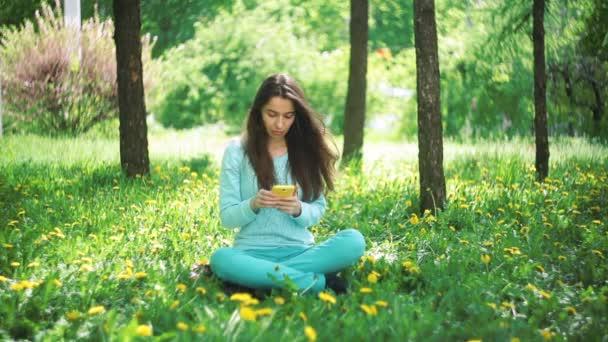 Šťastná žena s telefonem sedí na trávě