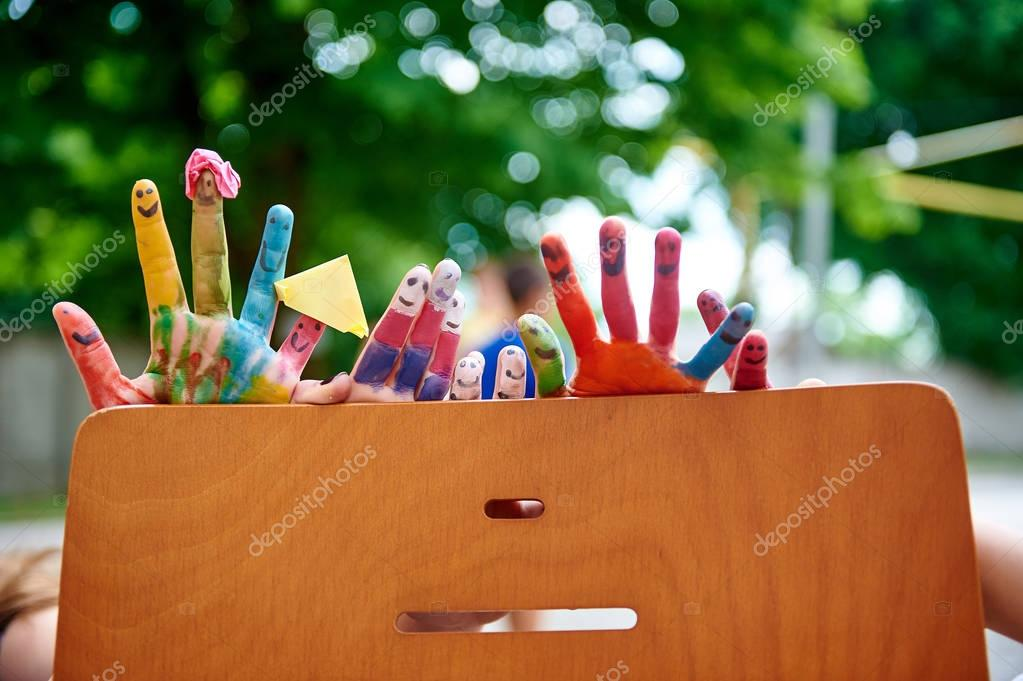 Childrens multicolored paints colored fingers