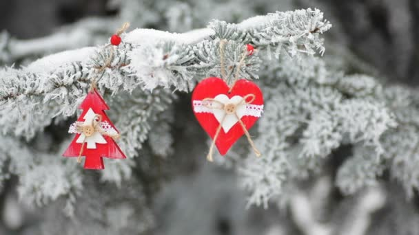 red Christmas toys on snowy fir branch in winter park