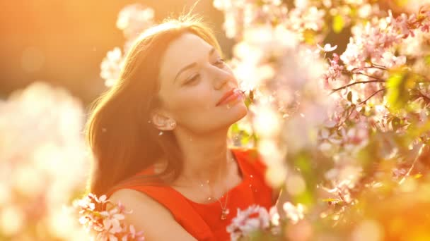 Animation video of Happy smiling young woman with spring flowers at garden