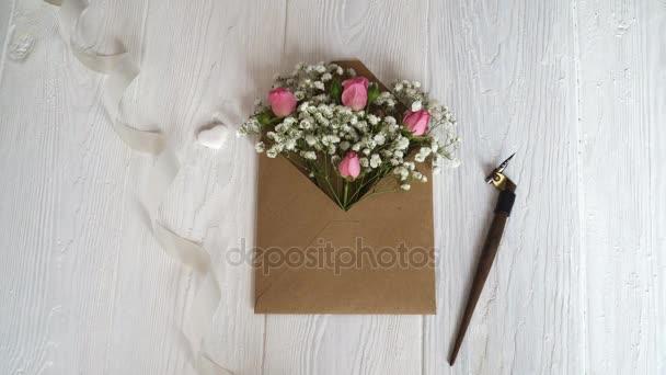 Kraft obálka s květinami na dřevěné bílé pozadí s kaligrafické pero