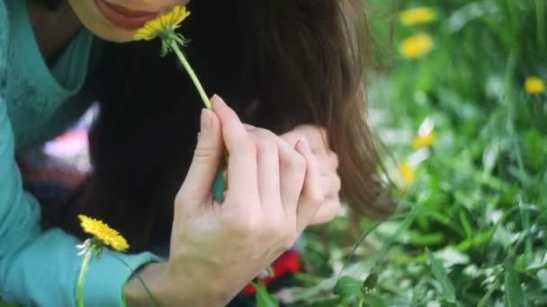 Krása ženy v louce. Krásná mladá dívka venku. Užijte si přírody. Zdravá usmívající se dívka leží na zelené trávě s divokými květy. Veselá a šťastná