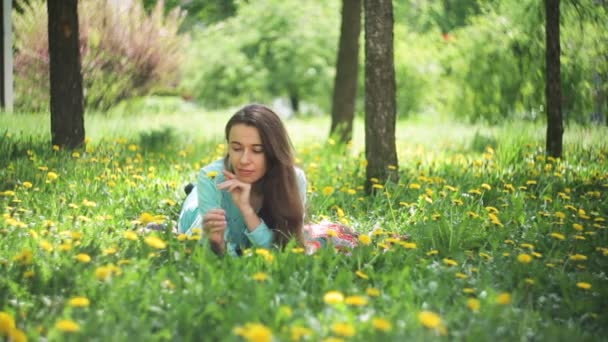 Beauty Woman in the Meadow. Beautiful Young Girl Outdoors. Enjoy Nature. Healthy Smiling Girl lying on Green Grass with wild Flowers. Laughing And Happy