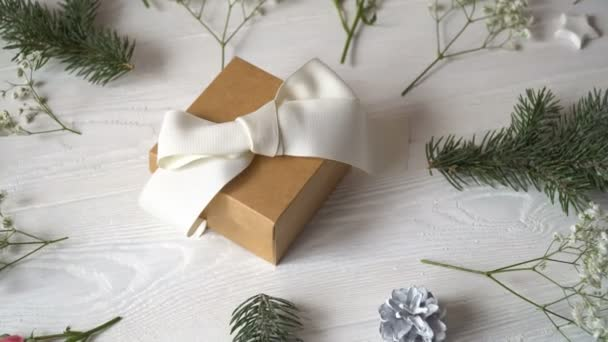 Kraft gift with white bow and flowers for greeting card for St. Valentines Day or wedding in rustic style with place for your text, Flat lay, top view