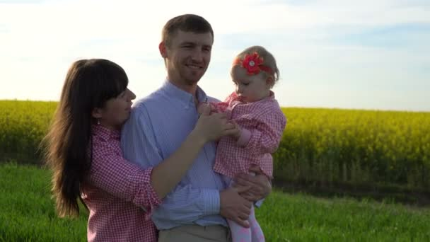 Motion video happy family: father, mother and daughter having fun outdoors in field in summer